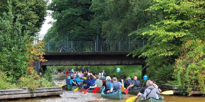 Mehrere Kanus, die über einen Fluss und unter einer Brücke durch fahren. An den seiten des Flusses sind grüne Bäume zu sehen.