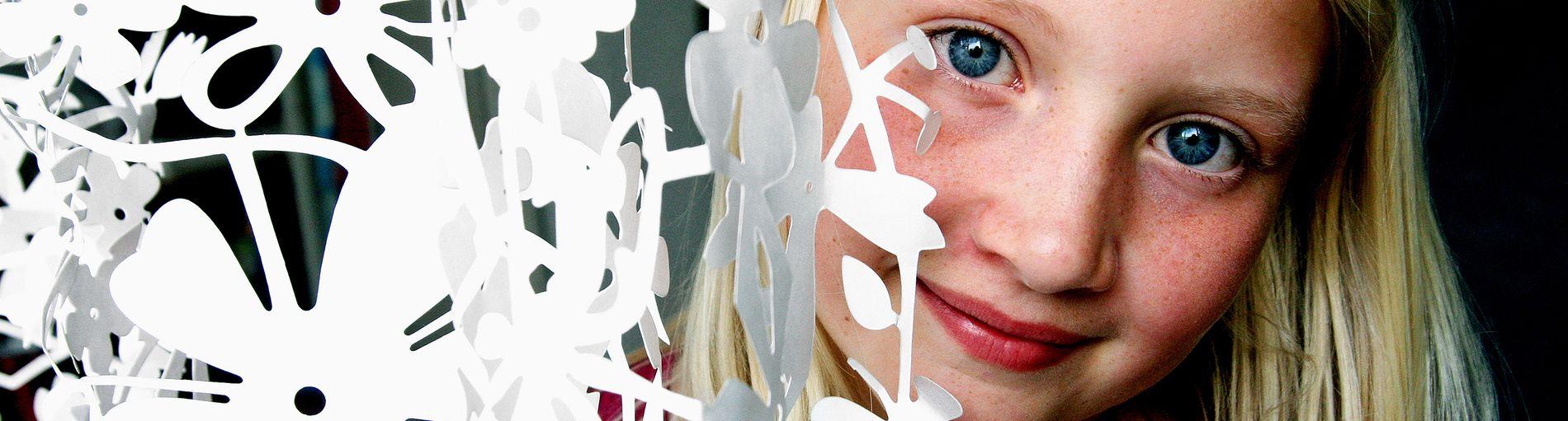 Ein Mädchen steht neben einer weißen Papiergirlande mit Blumenmotiven.