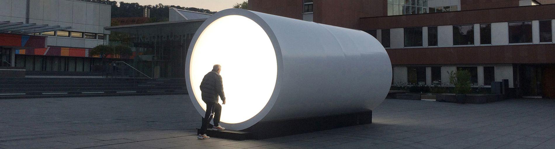 Ein weißes großes Rohr, welches beleuchtet wird.