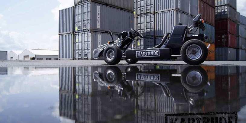 Ein Fahrzeug der Kartbude vor einigen Containern.