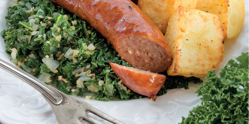 Ein Teller mit Kohl, Kochwurst und Bratkartoffeln