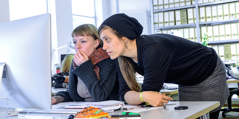 Zwei junge Frauen am Schreibtisch schauen auf einen Monitor.
