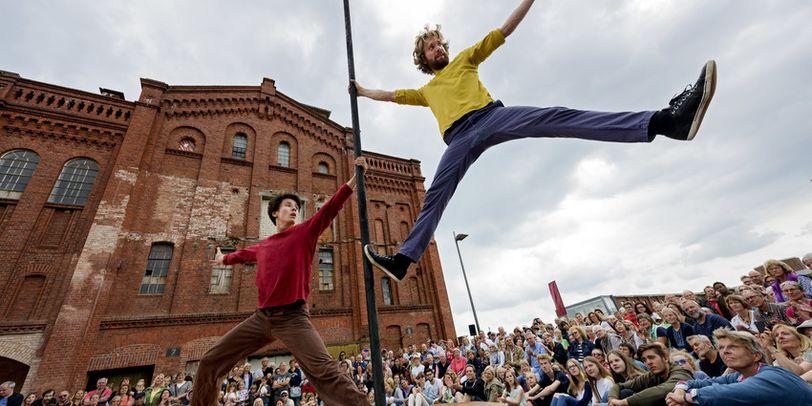 Zwei Männer, die an einer Stange über ihrem Publikum hängen