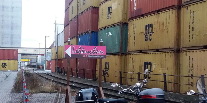 Auf einem Wegweiser-Schild steht die Lebkuchen-Manufaktur ausgeschildert. Im Hintergrund stapeln sich die großen bunten Container in der Überseestadt.