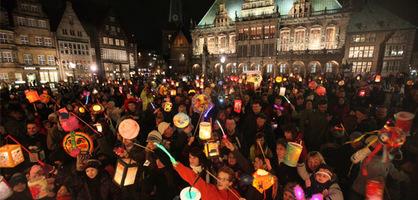 Kinder und Erwachsene stehen mit Laternen auf dem Bremer Marktplatz.
