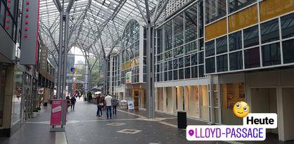 """Zu sehen ist ein langer überdachter Gang, in dem Personen stehen und durchlaufen. Rechts und links des Gangs sind verglaste Gebäudereihen zu erkennen. Außerdem ist im rechten Bildrand ein Schriftzug zu sehen: """"Heute. Lloyd-Passage"""" sowie ein kleines, gelbes animiertes Gesicht."""