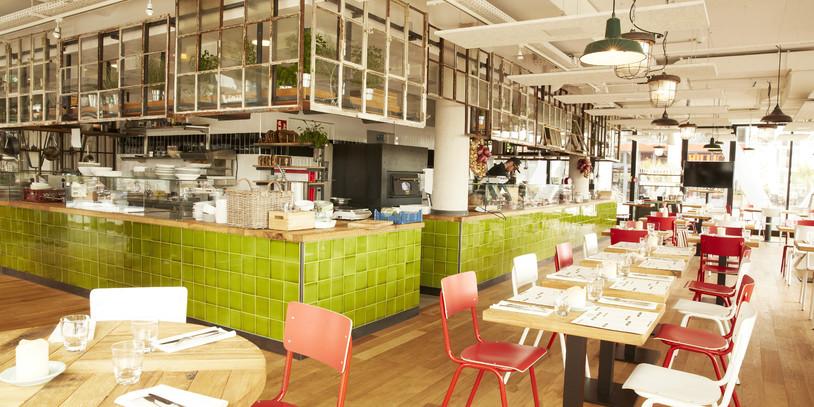 Die Innenräume eines großen Restaurants mit grün gefliester Theke und zahlreichen gedeckten Tischen.