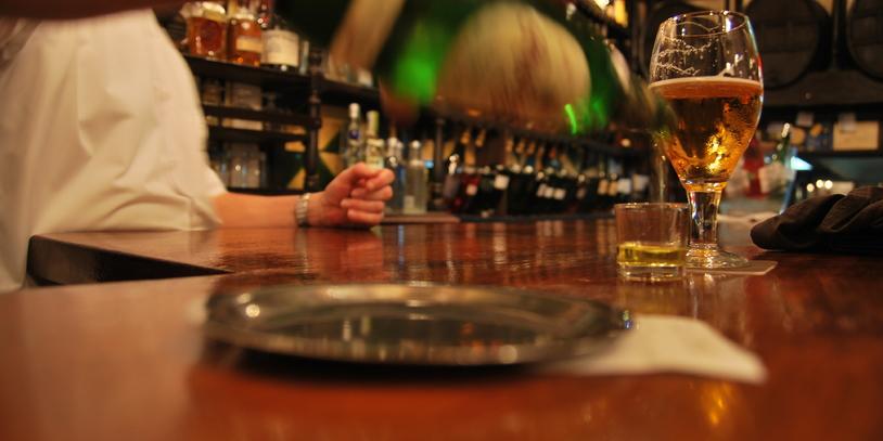 Kellner gießt ein Glas Bier ein