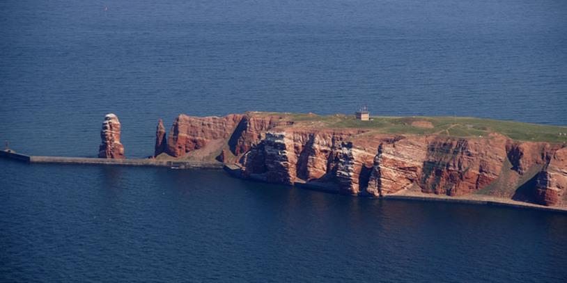 """Eine Luftaufnahme der roten Gesteinsklippen mit der """"Langen Anna"""" links im Bild. Quelle: Kurverwaltung Helgoland"""