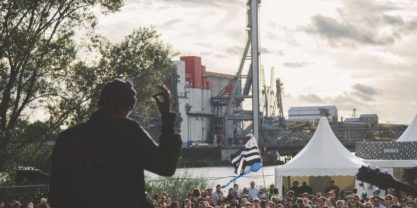 Auf dem MS Dockville Festival 2017. Blick von der Bühne auf das Publikum. Im Hintergrund sind Industrieanlagen.