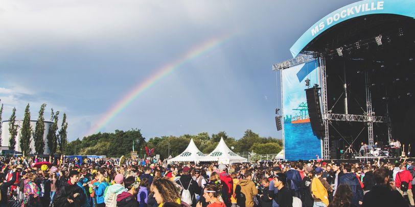 Das MS Dockville Festival mit der Hauptbühne. Davor sind viele Besucher. Am Himmel ist ein Regenbogen.
