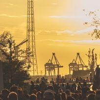 Das MS Dockville Festival. Viele Besucher vor einer Kulisse mit Schiffskränen und Industrie