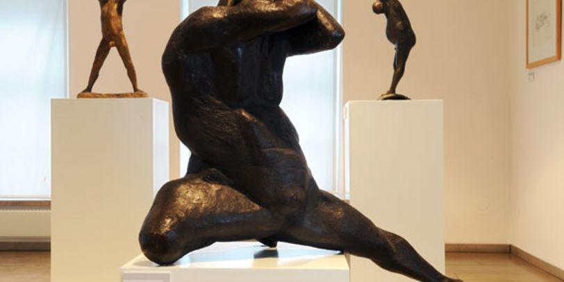 Drei Bronzefiguren von Gerhard Marcks - Grizmek. Die Figur im Vordergrund hat eine athletische Pose mit gespreizten Beinen.