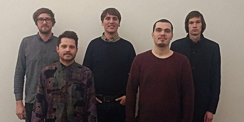 Eine Gruppe junger Männer steht vor einer weißen Wand und guckt in die Kamera.