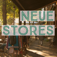 """Ein sonniges Bild aus dem Viertel. Links steht eine Kleiderstange und auf dem Foto steht """"Neue Stores"""""""