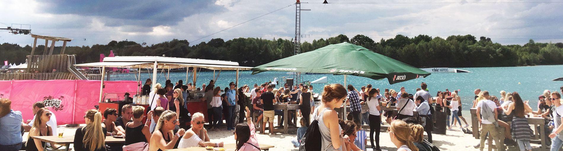 Zahlreiche Menschen sitzen auf Holzbänken an einem See. Der blaue Himmel ist wolkig