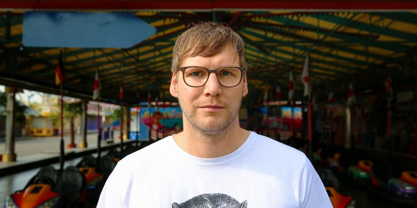 Ein Mann mit Brille steht vor einem Auto Scooter.