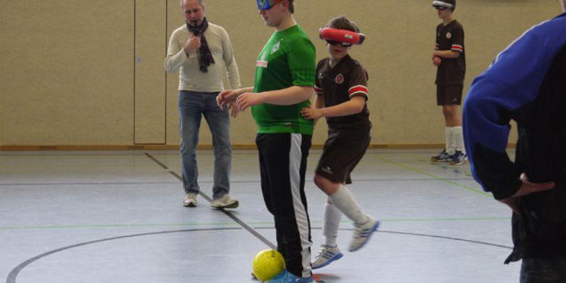 Blinde Mädchen und Jungen beim Fußballspielen