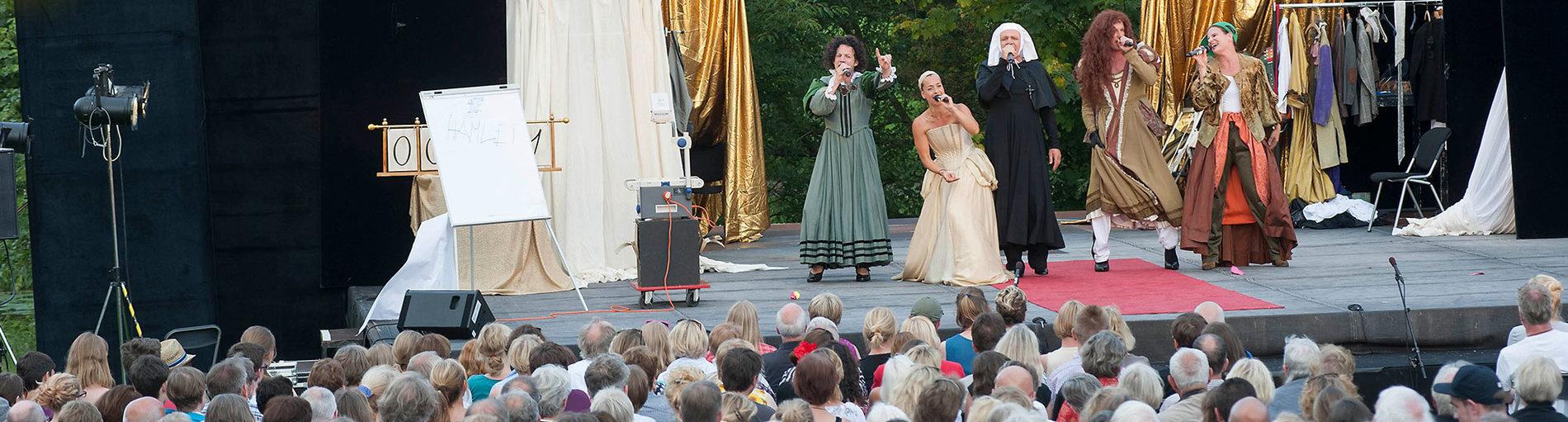 Bühne im Bürgerpark mit Schauspielern darauf und Zuschauern davor.