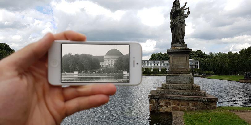 Zu sehen ist eine Hand, die ein weißes Smartphone festhält. Auf dem Bildschirm sind Bäume sowie die runde Kuppel eines Gebäudes in schwarz-weiß zu sehen. Der Rest des Bildes zeigt Wasser und rechts im Bild die steinerne Statue einer Frau. Im Hintergrund ist ein flaches, weißes Gebäude zu erkennen.