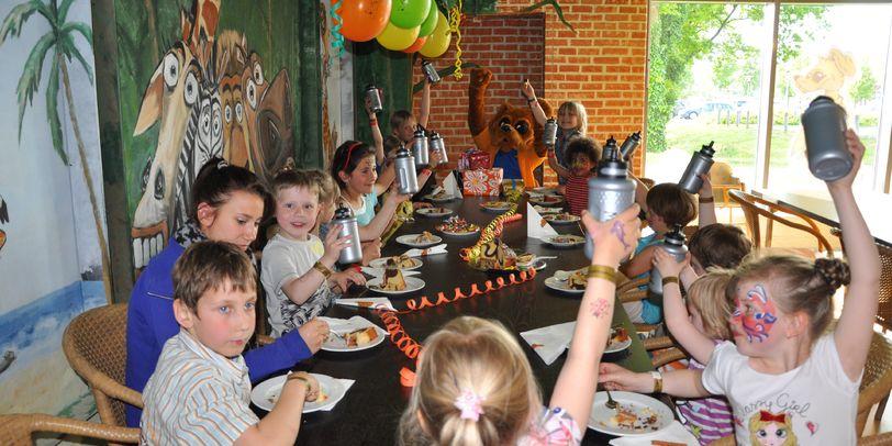 Glückliche Kinder sitzen an einem geschmücktem Tisch und essen Kuchen