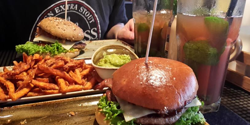 Zwei Burger mit Süßkartoffelpommes und Avocado-Dip, rechts im Bild sind zwei Cocktails zu sehen.