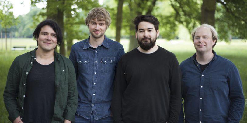 Die vier männlichen Bandmitglieder stehen auf einer Wiese.