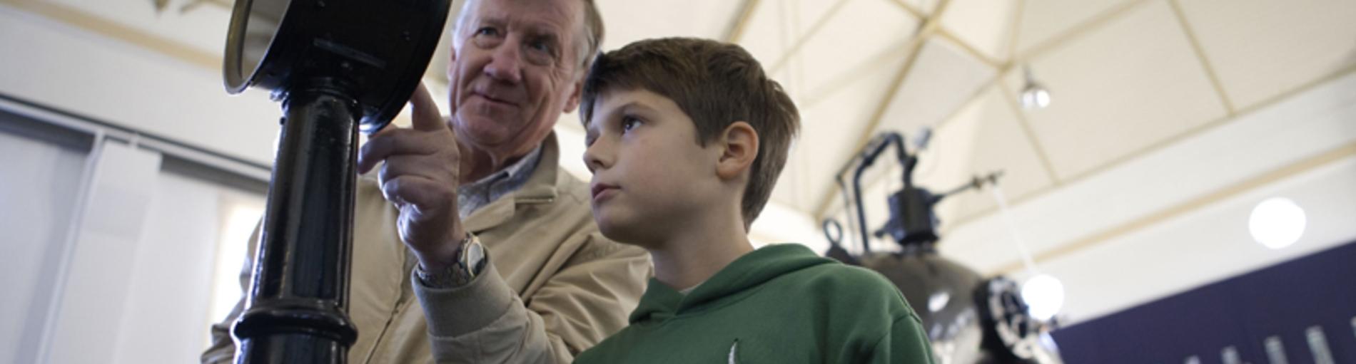 Großvater und Enkel betrachten ein Exponat im Museum