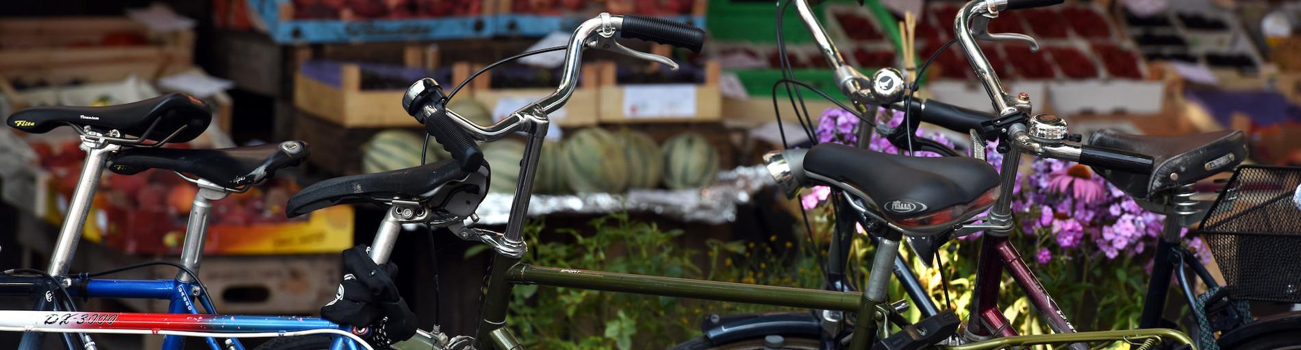 Parkende Fahrräder, im Hintergrund ein Obst- und Gemüsegeschäft mit Warenkörben vor dem Fenster.