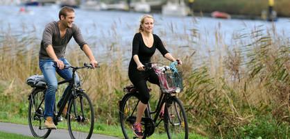 Ein Mann und eine Frau fahren Rad an der Weser; Foto: WFB Wirtschaftsförderung Bremen GmbH / Ingo Wagner