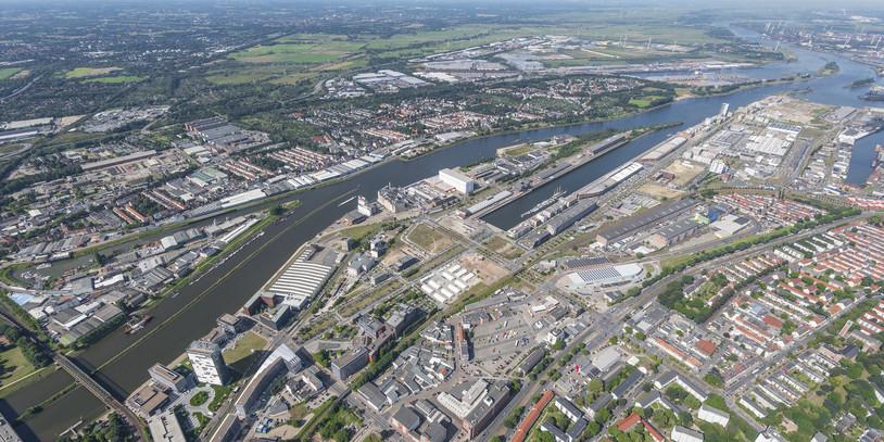 Vogelperspektive auf eine Stadt, in der Mitte ein Fluss; Quelle: WFB/Studio B