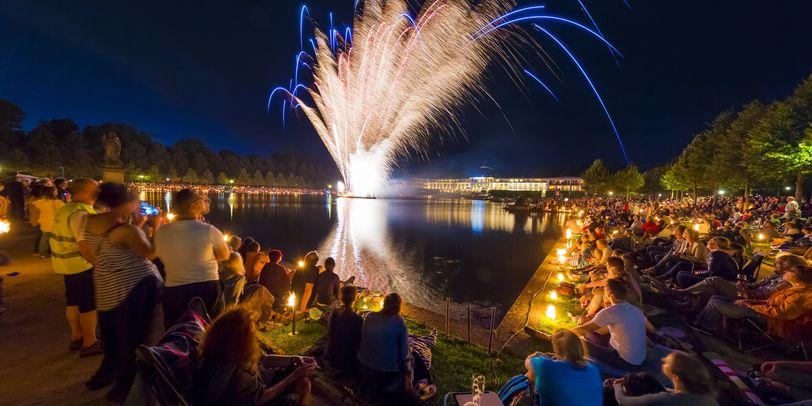 Menschen sitzen um den Hollersee und beobachten das Feuerwerk über dem See