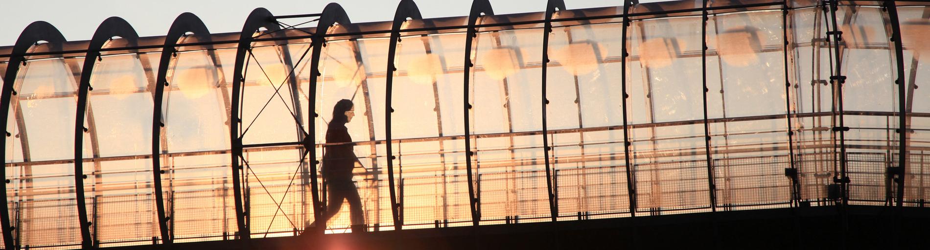 Ein transparenter Röhrengang in dem man die Silhouette einer Person sieht bei untergehender Sonne.