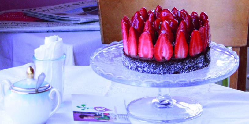 Ein Schokoladen-Erdbeerkuchen, daneben Kaffeegeschirr, alles auf einer lila Tischdecke; Quelle: Radieschen