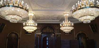 An der Decke hängen vier große Kronleuchter, die mit Diamanten besetzt sind. Die Decke selbst ist weiß und mit Ornamenten verziert. Der Raum wird von einem runden Tisch ausgefüllt, an dem zahlreiche Stühle stehen. Auf der gegenüberliegenden Seite befindet sich eine große hölzerne Tür, die mit goldenen Ornamenten verziert ist.