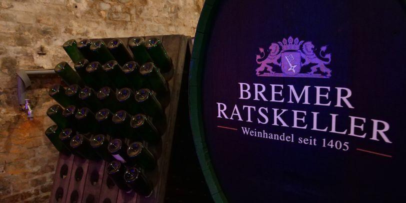Ein großes Weinfass im Bremer Ratskeller, daneben viele Weinflaschen