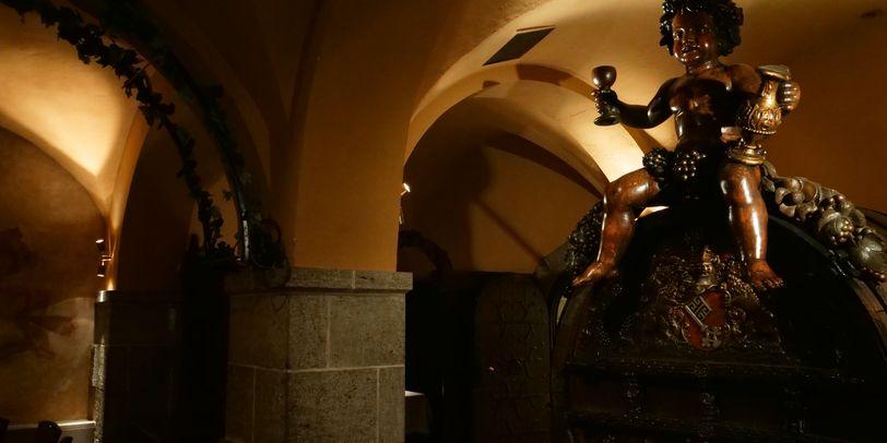 Der Festsaal im Bremer Ratskeller. Darin ein sehr großes Weinfass mit einer Statue die auf dem Fass sitzt