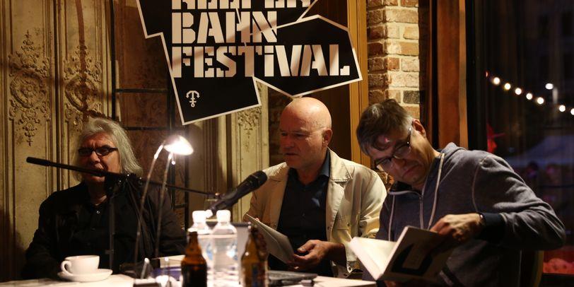 Eine Lesung auf dem Reeperbahnfestival 2016. Drei Männer sitzen mit Büchern und Zetteln vor einem Mikrofon.