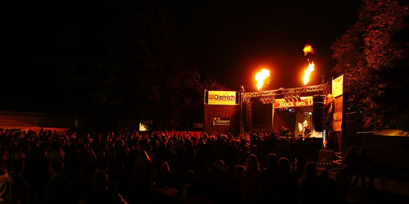 Die Bühne auf dem Rock den Deich Festival in der Nacht. Darauf ein singender Künstler vor dem Publikum. Über der Bühne sind Flammen.