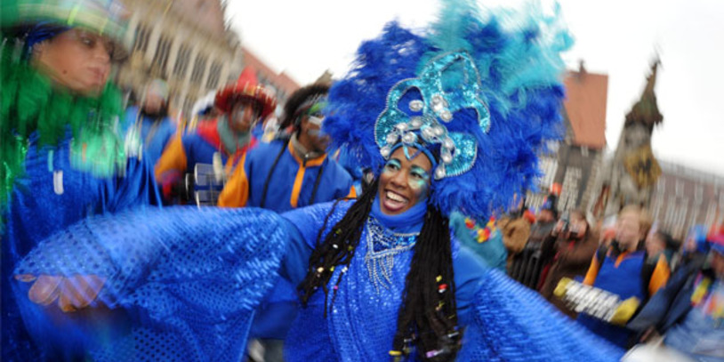 Tanzende Frau im blauen Kostüm beim Karneval.