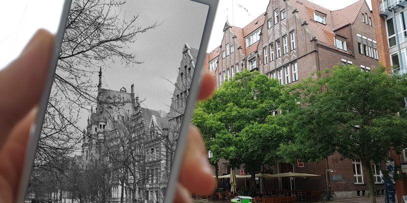 Zu sehen ist eine Hand, die ein weißes Smartphone festhält, auf dessen Bildschirm in schwarz-weiß eine Häuserreihe mit spitzen Giebeln sowie Bäume zeigt. Rechts im Bild stehen grüne Bäume und braune Häuser mit spitzen Giebeln.