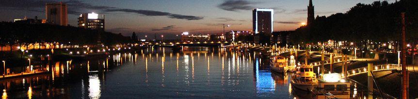 Blick auf die Weser an der Schlachte bei abendlicher Dunkelheit. Die Lichter spiegeln sich auf dem Wasser.