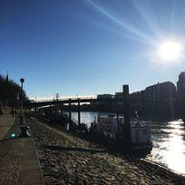 Zu sehen ist ein gepflasterter Fußweg, auf dem Personen spazieren gehen. Schräg abfallende Steine führen zum Wasser. Auf dem Wasser, das rechts im Bild zu sehen ist, liegt ein Schiff. Im hinteren Teil des Bildes ist eine Brücke zu erkennen, die über das Wasser führt.