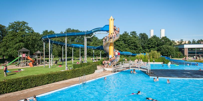 Blick auf Rutsche, Spielplatz und Schwimmbecken im Schloßparkbad