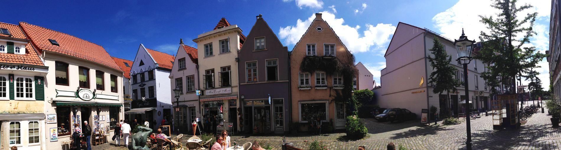 Zu sehen ist ein kleiner Platz, auf dem Menschen an Tischen sitzen und Getränke trinken. Der Platz ist umgeben von bunten Häusern. Rechts im Bild stehen eine Laterne und eine gelbe Telefonzelle.