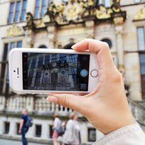 Zu sehen ist eine Hand, die ein Handy hält. Auf dem Handybildschirm ist der Ausschnitt eines Gebäudes zu erkennen. Dieses Gebäude sieht man auch im Hintergrund des gesamten Bildes. Es hat eine goldene Fassade und Treppen.