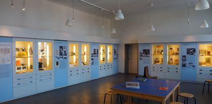 Ein Ausstellungsraum im Schulmuseum in Bremen. In der Mitte steht ein Tisch mit Büchern, an den Wänden sind Ausstellungsvitrinen und Plakate