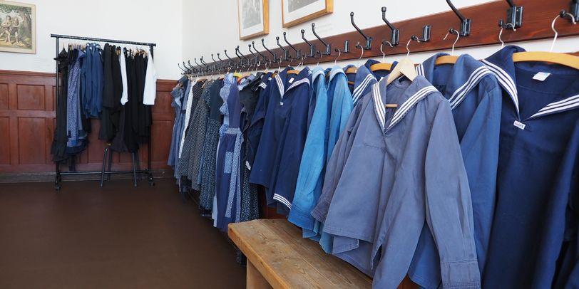 Alte Schuluniformen im Schulmuseum Bremen. Die Uniformen hängen aufgereiht an der Wand, unterteilt in Uniformen für Jungs und Uniformen für Mädchen