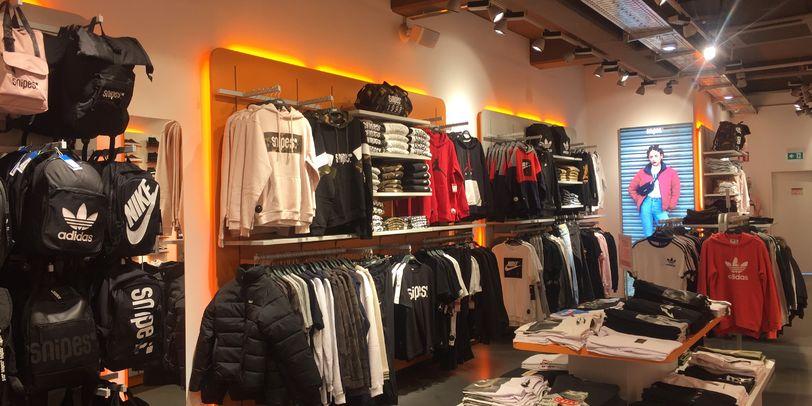 Sportklamotten und Rucksäcke verschiedener Marken Händen in einem weitläufigen Raum