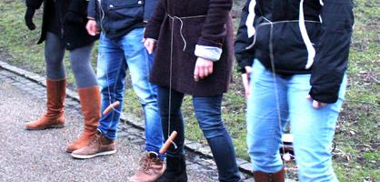 Menschen schwingen eine Wurst zwischen ihren Beinen
